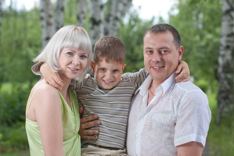 Familia feliz con el hijo en el parque imágenes de archivo libres de regalías
