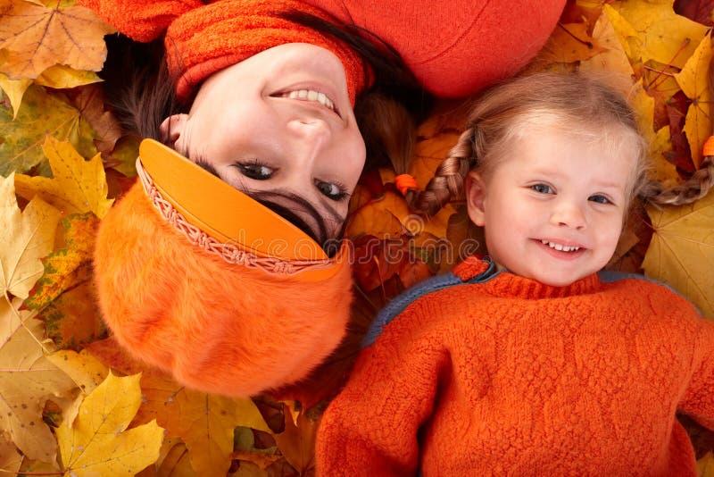 Familia feliz con el niño en la hoja de la naranja del otoño.