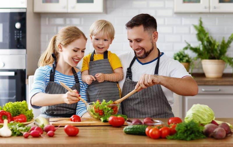 Familia feliz con el niño que prepara la ensalada vegetal imagenes de archivo