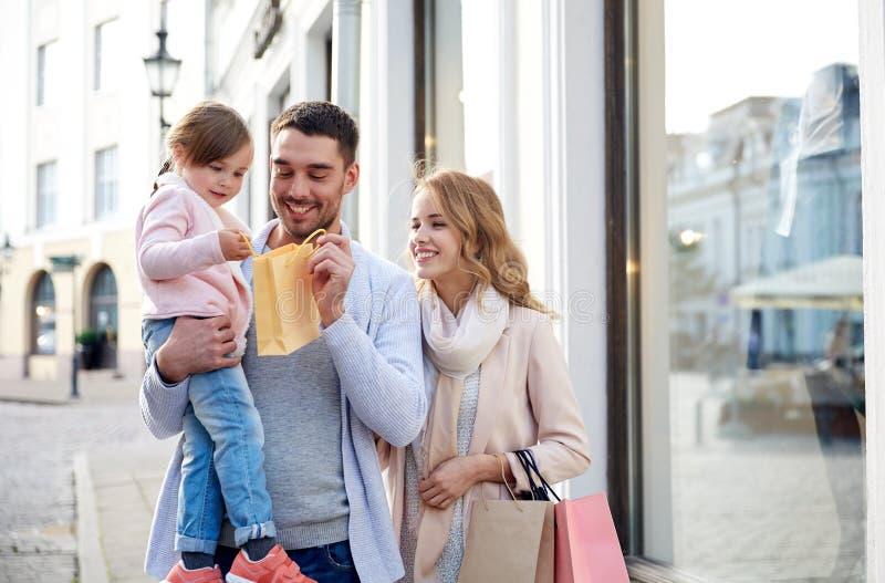 Familia feliz con el niño y los panieres en ciudad imagen de archivo libre de regalías