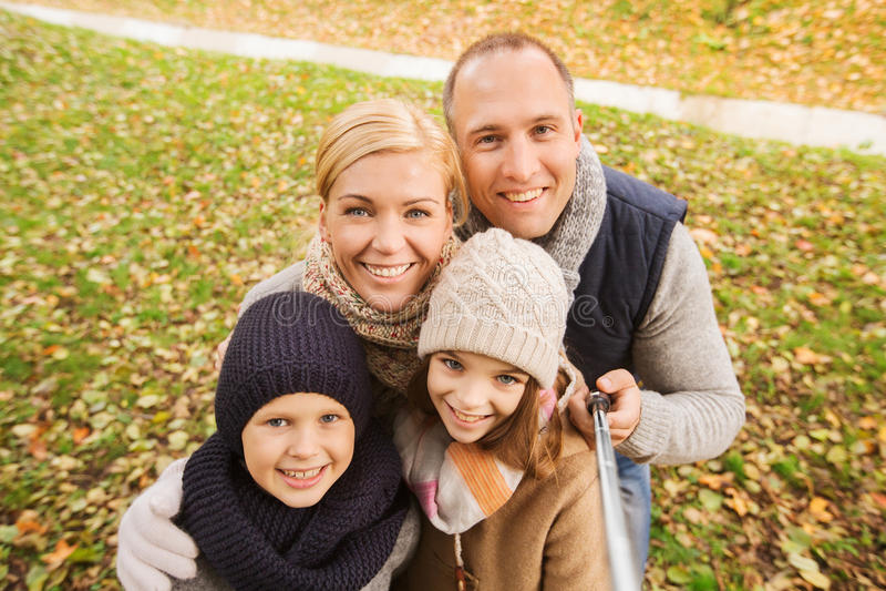 Familia feliz con el palillo del selfie en parque del otoño foto de archivo