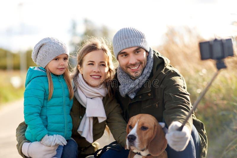 Familia feliz con el perro que toma el selfie en oto?o fotos de archivo