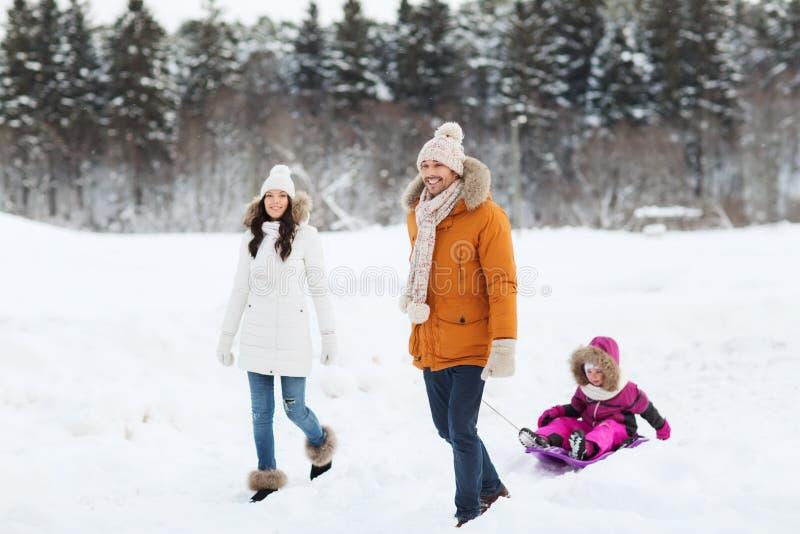 Familia feliz con el trineo que camina en bosque del invierno imagenes de archivo
