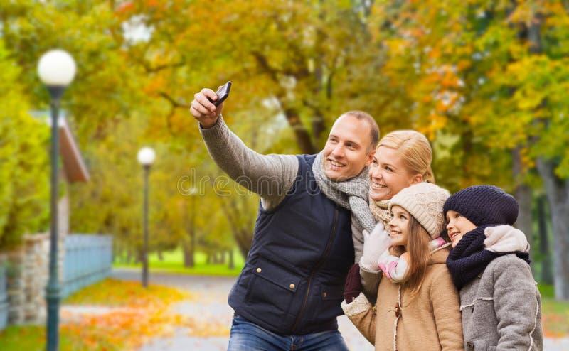 Familia feliz con la c?mara en parque del oto?o foto de archivo