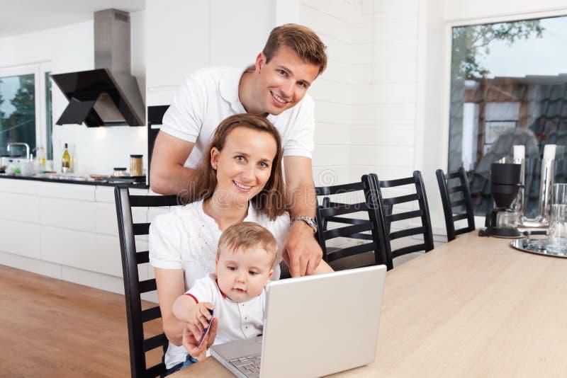 Familia feliz con la computadora portátil fotos de archivo