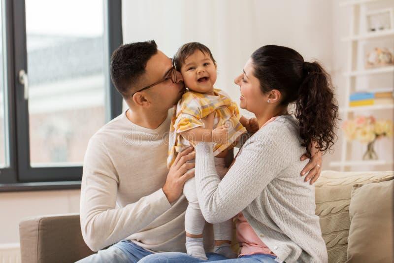 Familia feliz con la hija del bebé en casa foto de archivo