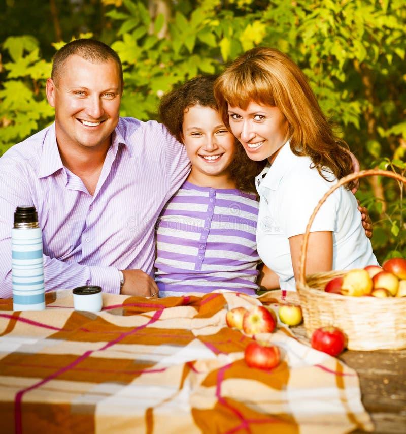 Familia feliz con la hija en comida campestre del otoño fotos de archivo