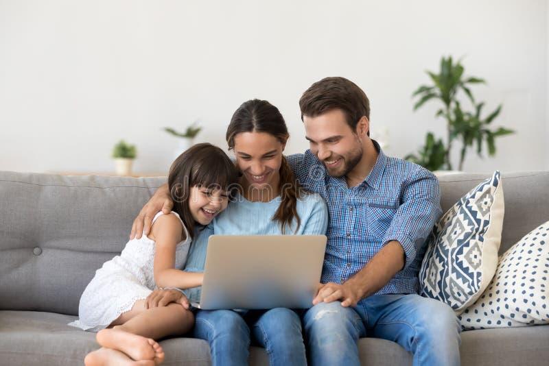 Familia feliz con la muchacha del niño que se divierte usando el ordenador portátil junto fotos de archivo libres de regalías