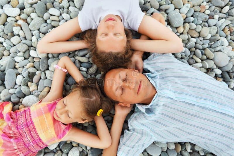 Familia feliz con la niña que miente en la playa pedregosa imágenes de archivo libres de regalías