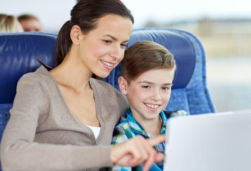Familia feliz con la PC de la tableta que se sienta en autobús del viaje imagenes de archivo