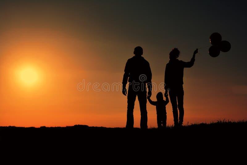 Familia feliz con la silueta de los globos en una colina en la puesta del sol fotos de archivo