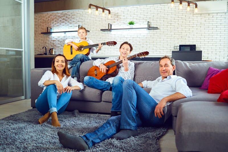 Familia feliz con las canciones del canto de la guitarra que se sientan en el cuarto foto de archivo