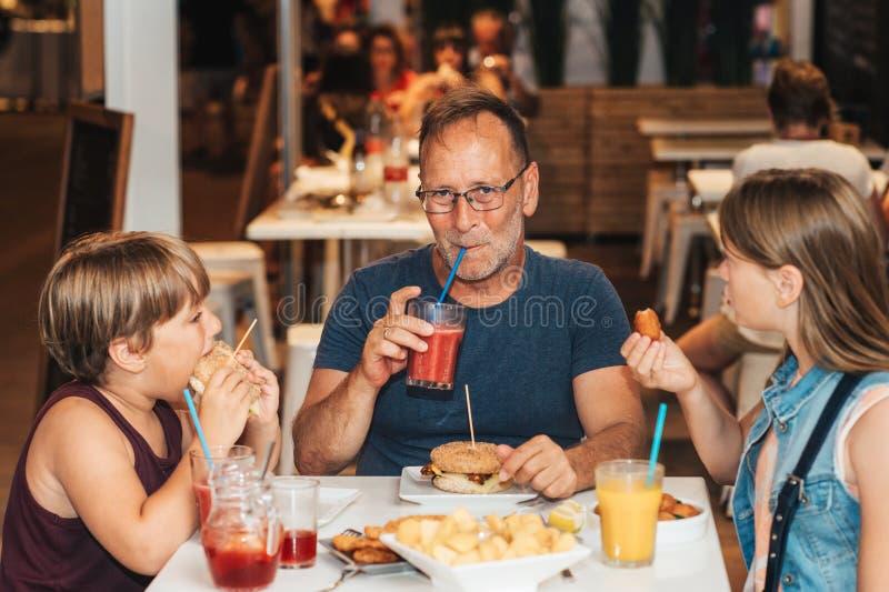 Familia feliz con los niños en restaurante al aire libre imagen de archivo