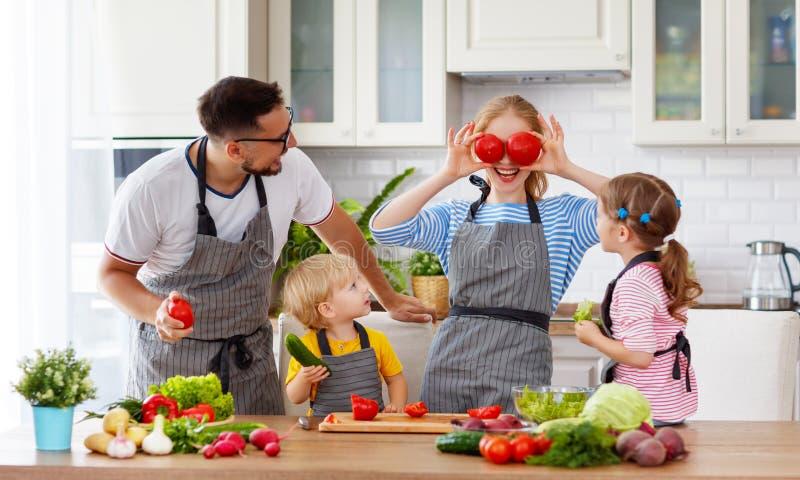 Familia feliz con los niños que preparan la ensalada vegetal fotografía de archivo
