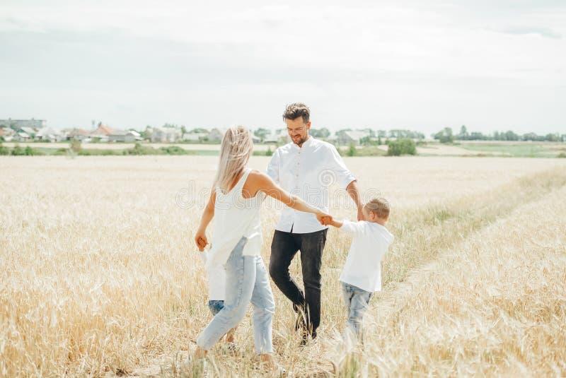 Familia feliz con los niños que tienen baile redondo de la diversión que lleva a cabo las manos juntas en campo de trigo fotos de archivo