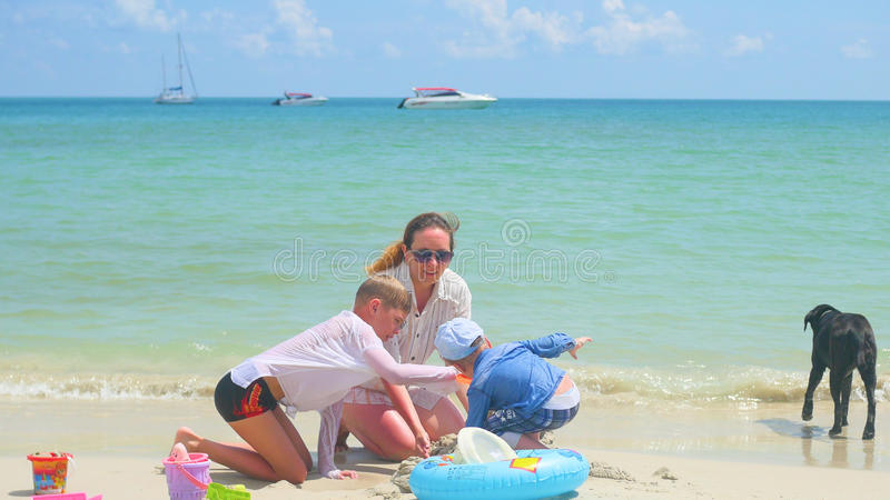 Familia feliz con los niños y el perro que juegan en la playa arenosa con los juguetes Isla tropical, en un día caliente fotos de archivo
