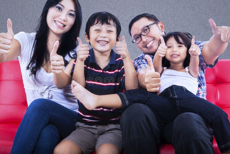 Familia feliz con los pulgares para arriba foto de archivo