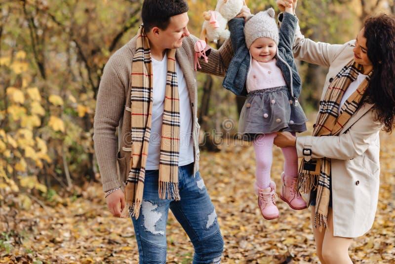 Familia feliz con poco paseo del bebé en el camino del parque con el árbol amarillo foto de archivo libre de regalías