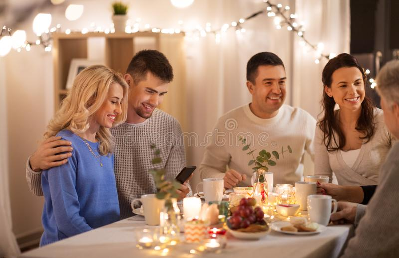 Familia feliz con smartphone en la fiesta del t? en casa foto de archivo
