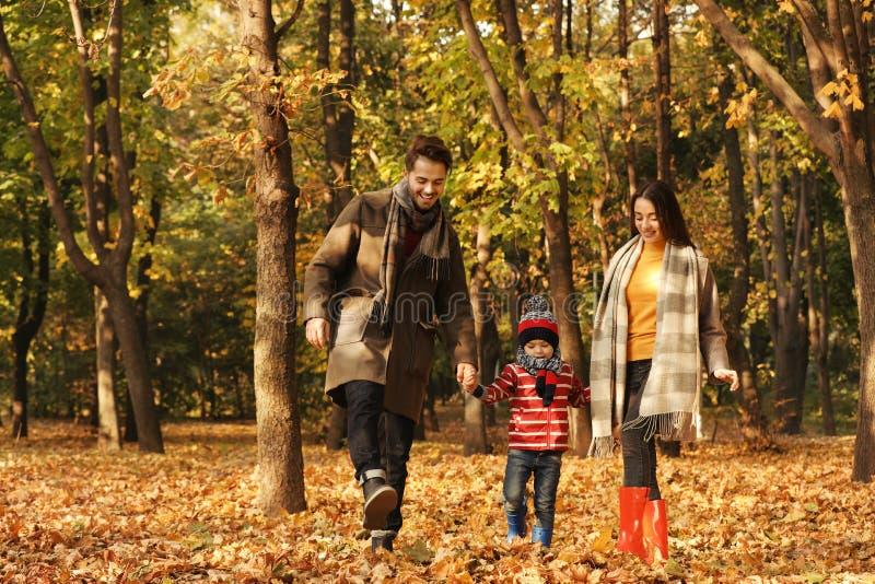 Familia feliz con tiempo del gasto del ni?o junto Autumn Walk imágenes de archivo libres de regalías