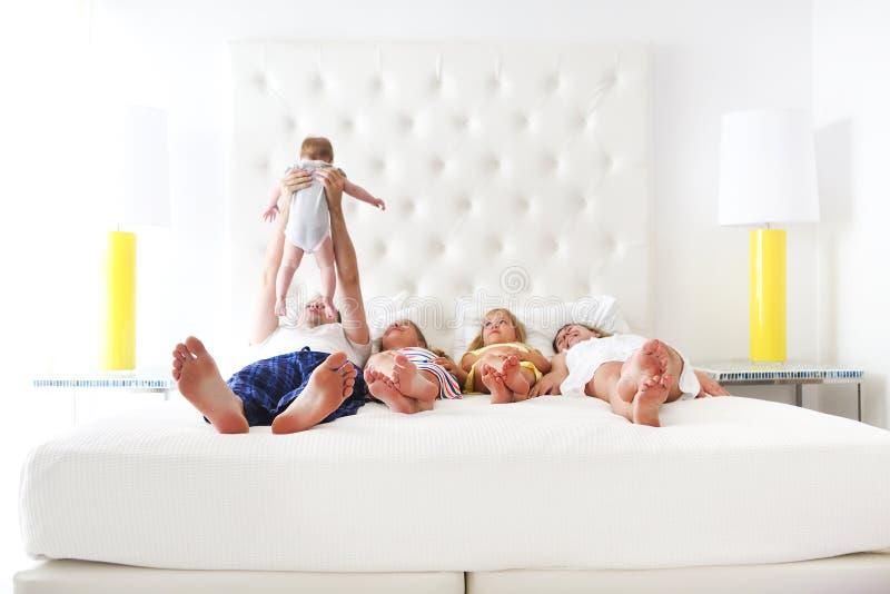 Familia feliz con tres niños en el dormitorio fotos de archivo