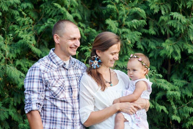 Familia feliz con una pequeña hija en un fondo de hojas verdes fotos de archivo