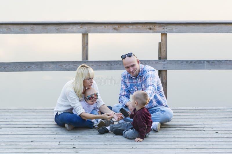 Familia feliz de dos padres y niños, uno muchachos, bebé, sentándose junto en el embarcadero del río fotos de archivo libres de regalías