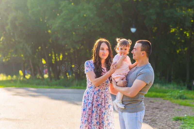 Familia feliz de la raza mezclada que presenta para un retrato en el parque imagen de archivo