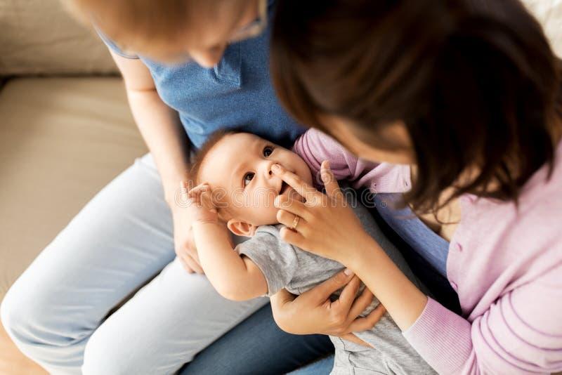 Familia feliz de la raza mixta con el hijo del beb? en casa imagen de archivo libre de regalías