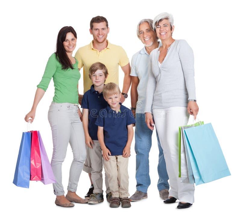 Familia feliz de las generaciones con los bolsos de compras fotos de archivo