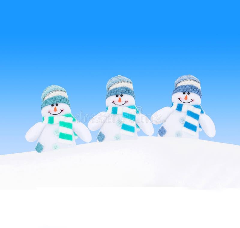 Familia feliz de los muñecos de nieve del invierno contra el cielo azul foto de archivo