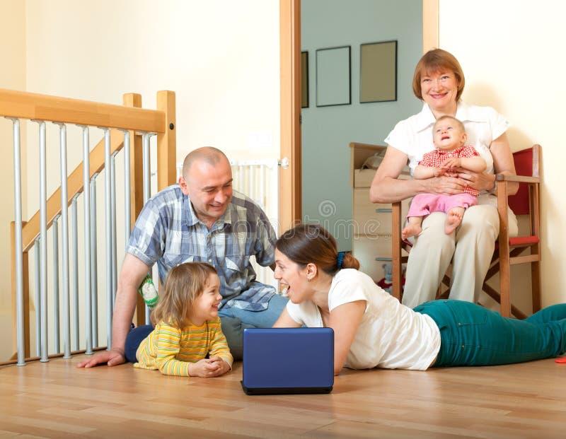 Familia feliz de los multigenerations con el ordenador portátil en casa imagen de archivo libre de regalías