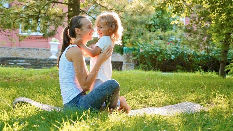 Familia feliz de madre deportiva joven y pequeña de hija linda que se divierten al aire libre imagen de archivo libre de regalías