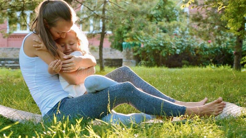 Familia feliz de madre deportiva joven y pequeña de hija linda que se divierten al aire libre fotos de archivo