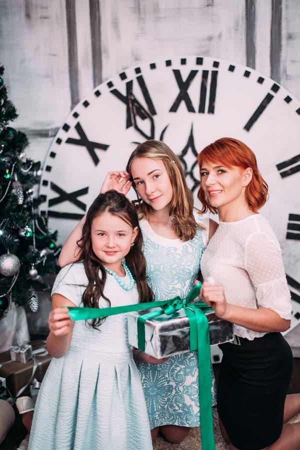 Familia feliz de madre y de hijas con los regalos de Navidad cerca del árbol de navidad con el reloj grande en el fondo que muest fotografía de archivo libre de regalías
