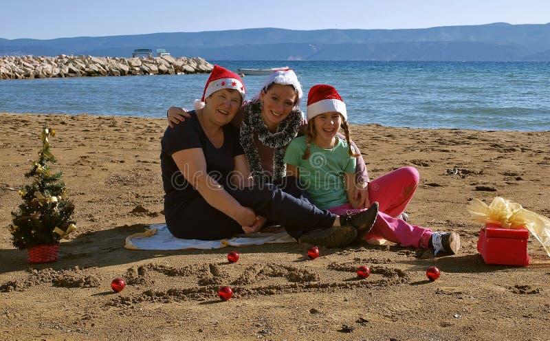 Familia feliz de Navidad en la playa fotos de archivo