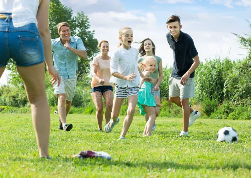 Familia feliz de seis personas que juegan feliz en fútbol junto imagen de archivo libre de regalías