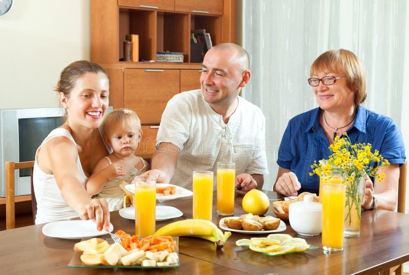 Familia feliz de tres generaciones de Loughting que come friuts y la bebida imagen de archivo