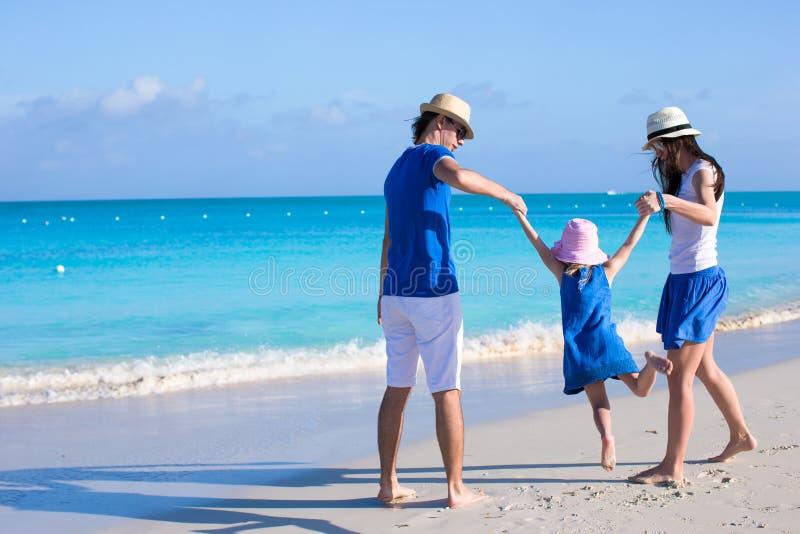 Familia feliz de vacaciones de goce de la playa tres imagen de archivo