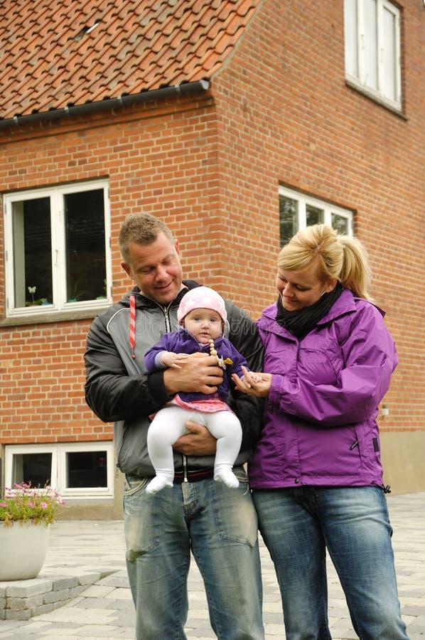 Familia feliz delante de la casa imágenes de archivo libres de regalías