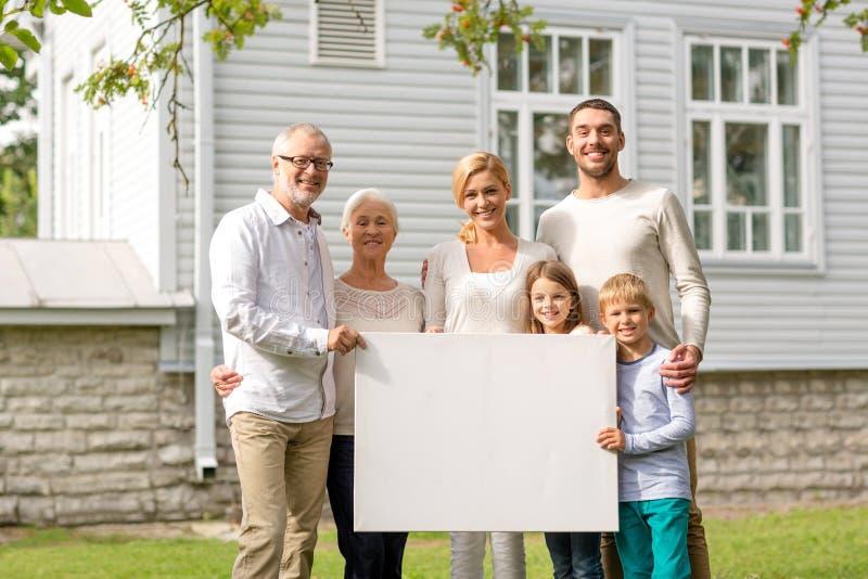 Familia feliz delante de la casa al aire libre foto de archivo