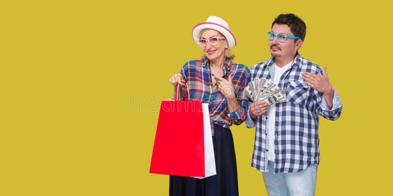 Familia feliz después hacer compras, de hombre adulto y de la mujer en la camisa a cuadros casual que se une, esposa que sostiene imágenes de archivo libres de regalías