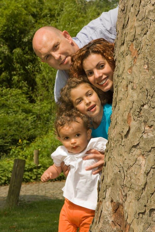 Familia feliz detrás de un árbol fotos de archivo libres de regalías