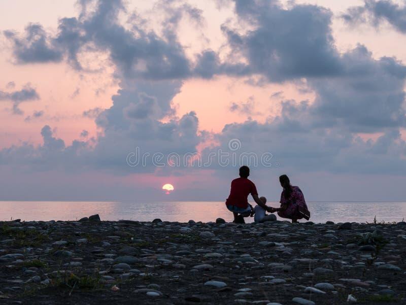 Familia feliz - el padre, madre, hijo del bebé ve la resaca del mar de la puesta del sol en la playa negra de la arena Padres act fotos de archivo libres de regalías