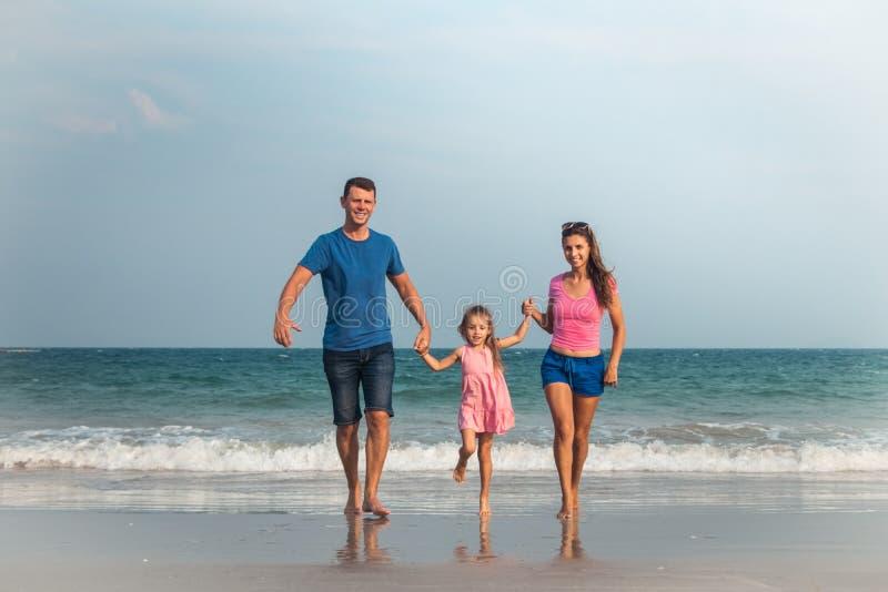 Familia feliz el vacaciones La mamá, el papá y una pequeña hija están caminando a lo largo de la costa Familia que viaja imagen de archivo