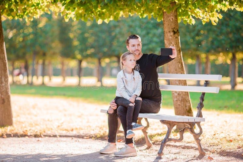 Familia feliz en caída El padre y el niño se divierten que toma el selfie en día hermoso del otoño imagen de archivo