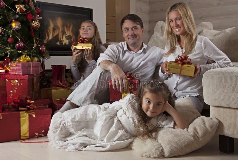 Familia feliz en casa con los regalos de la Navidad imagen de archivo libre de regalías