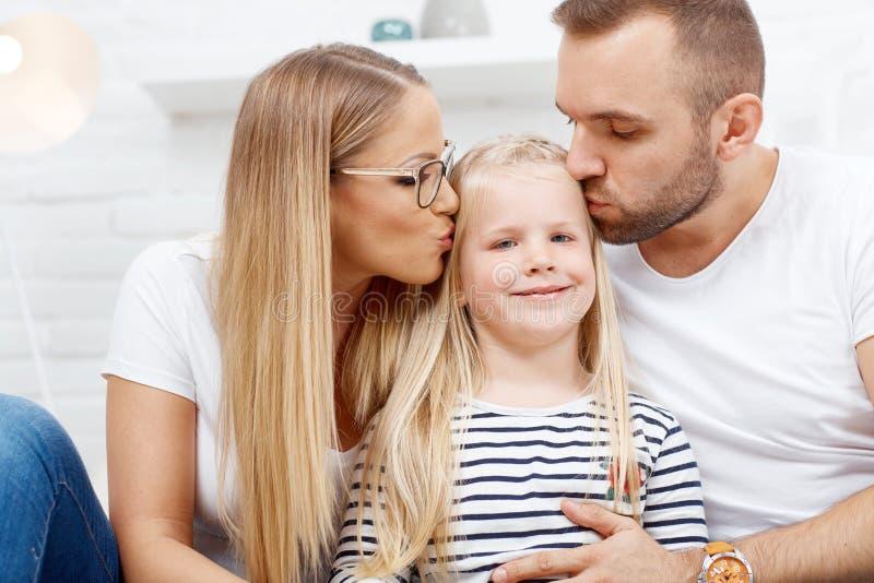 Familia feliz en casa en el amor que besa al niño foto de archivo