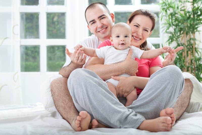 Familia feliz en casa en cama foto de archivo libre de regalías