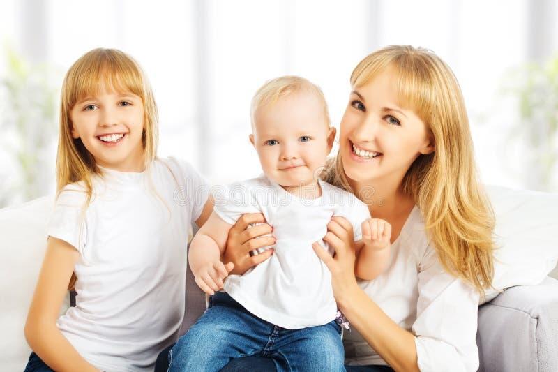 Familia feliz en casa en el sofá. Madre e hija e hijo foto de archivo